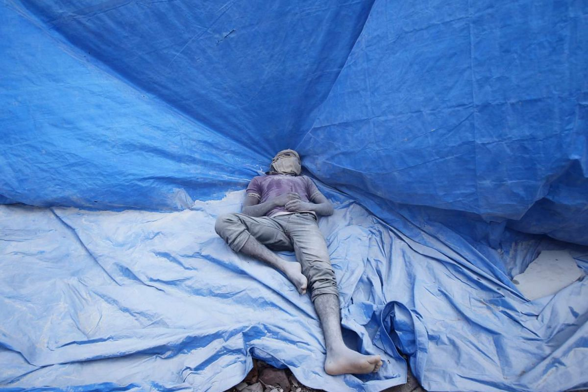 A worker with his face covered, rests on a tarpaulin at a construction site of a residential complex in Bengaluru, India, December 16, 2015. PHOTO: REUTERS