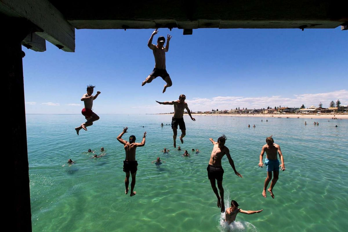 Swimmers jump off a jetty to escape the summer heat at Henley Beach, west of Adelaide, December 17, 2015. PHOTO: REUTERS