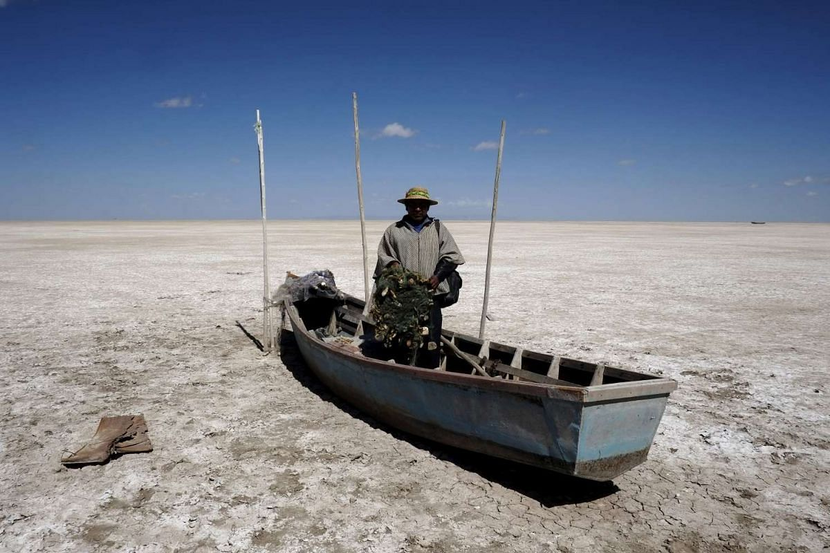 Fisherman Rene Valero from the Urus ethnic group is seen on his boat on the dried Poopo lakebed in the Oruro Department, south of La Paz, Bolivia, on Dec 17, 2015. Lake Poopo in Bolivia, the Andean nation's formerly second largest after the famed Tit