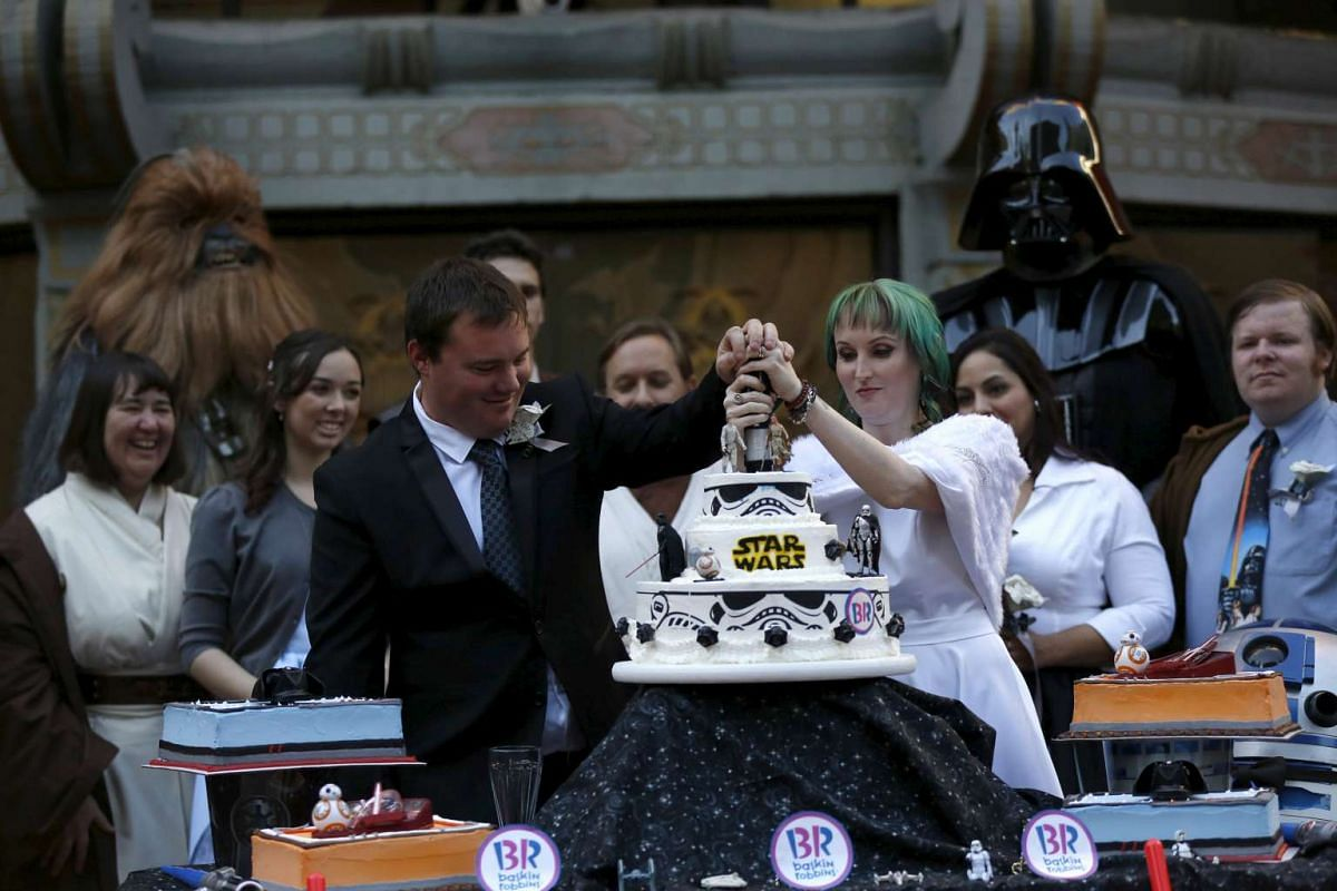 Andrew Porters and his wife Caroline Ritter from Australia cutting a cake at their wedding ceremony accompanied by people dressed as characters from Star Wars in the forecourt of the TCL Chinese Theatre in Hollywood, California, on Dec 17, 2015. PHOT