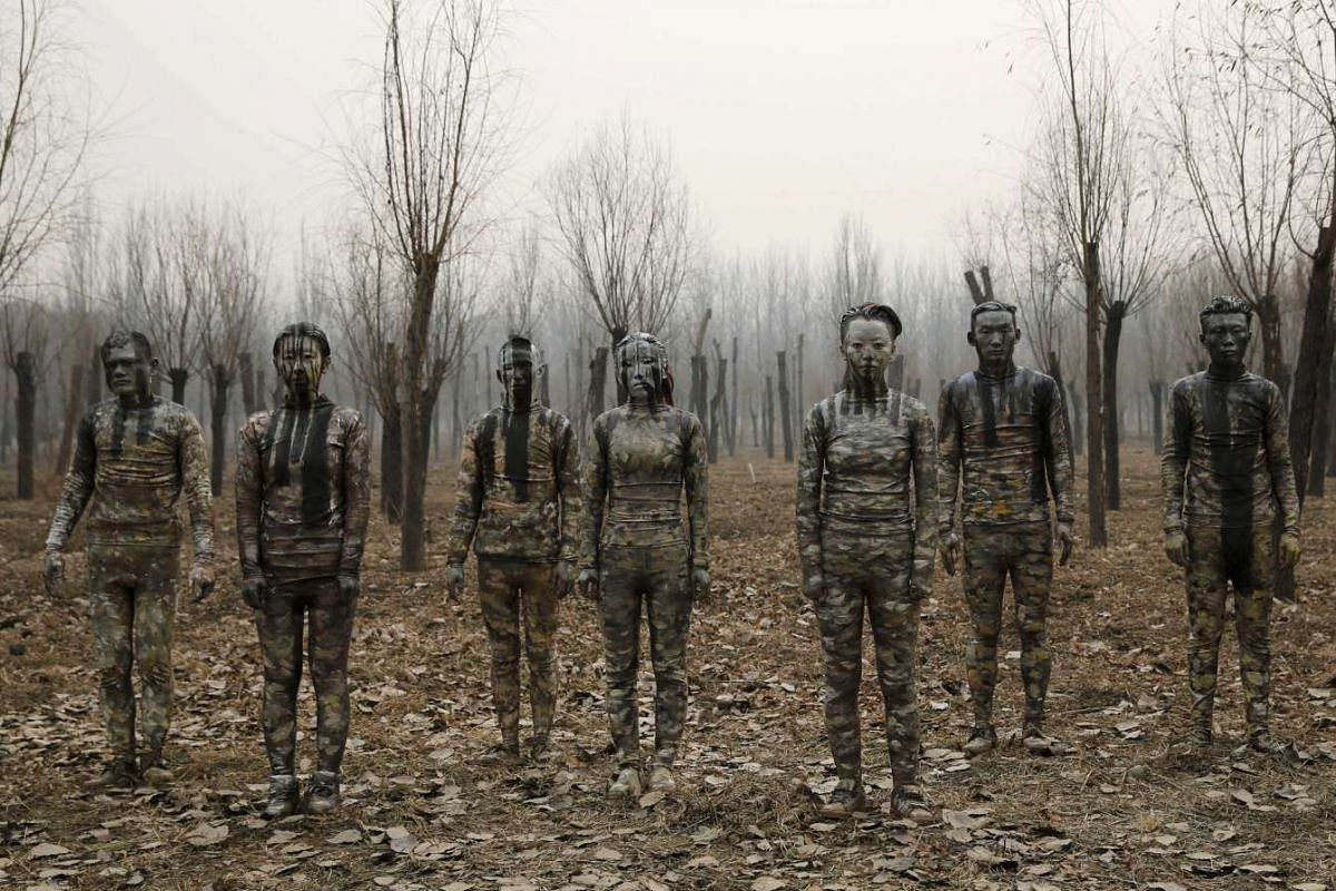 """Models painted in camouflage colours to blend in with the background pose for Chinese artist Liu Bolin's artwork """"Dongji"""" in Beijing, China, Dec 20, 2015."""