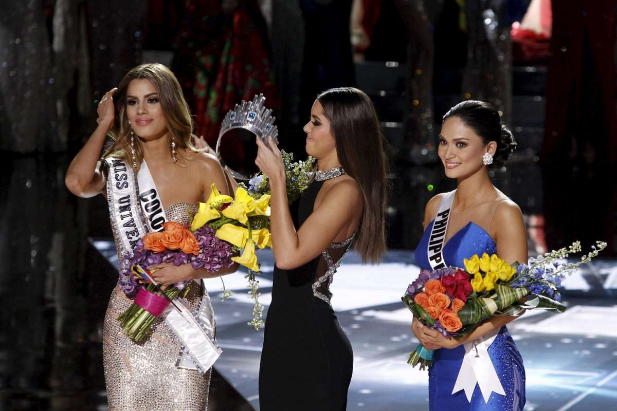 Miss Universe 2014 Paulina Vegas (centre) transfers the crown to winner Miss Philippines Pia Alonzo Wurtzbach (right) from Miss Colombia Ariadna Gutierrez.