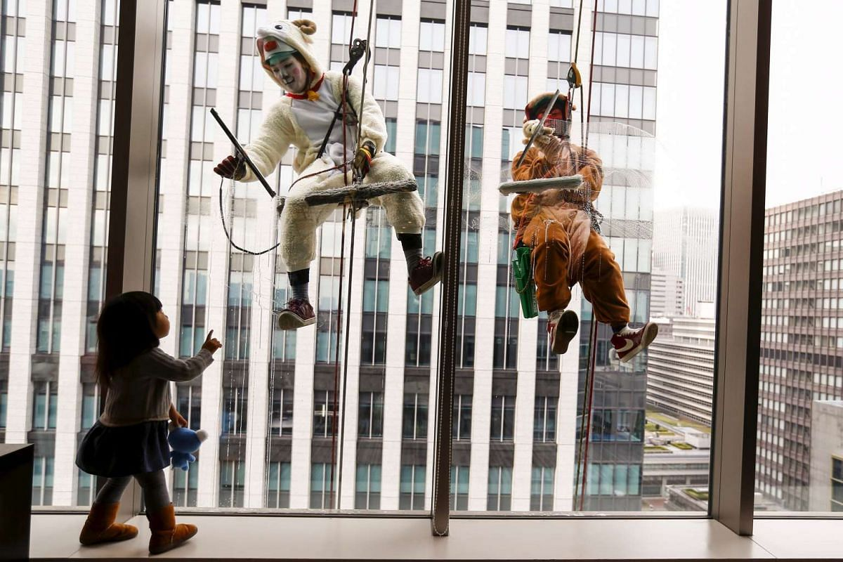 A child looks at window cleaners work while dressed in sheep and monkey costumes during an event marking the upcoming end of the year at a hotel in Tokyo, Japan on Dec 21, 2015.