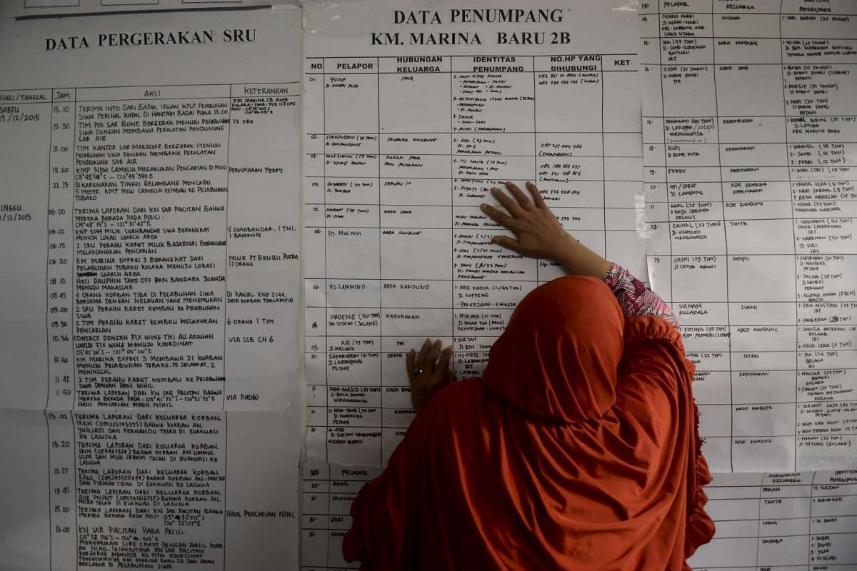 A woman leans against a ferry passenger list as she searches for information about family members who were on board a sunken ferry in Indonesia on Dec 21, 2015.