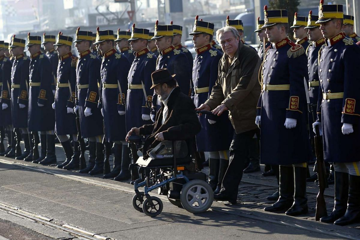 A disabled survivor of the 1989 anti communist uprising passes by the Presidential Honour Guard of Romania during an official commemoration ceremony.