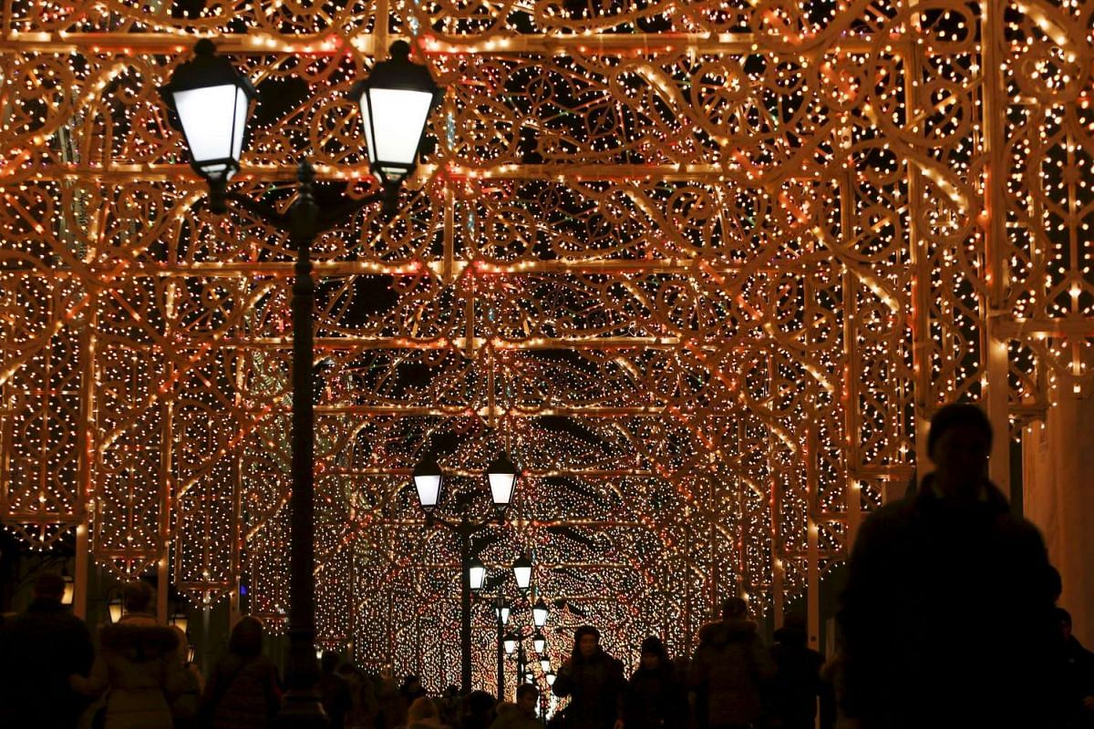 People walk along a street with Christmas and New Year decorations in Moscow.