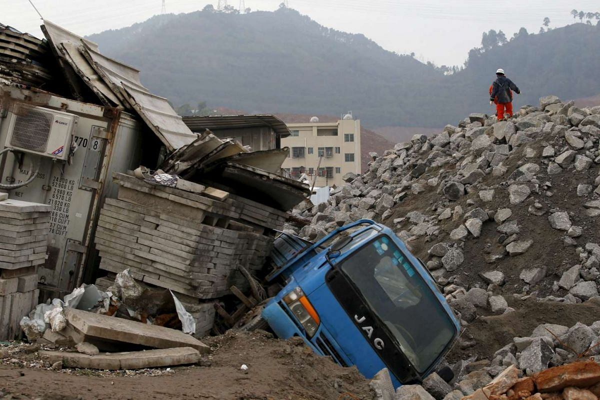 Rescue workers walk past a damaged vehicle in the industrial park hit by a landslide in Shenzhen.