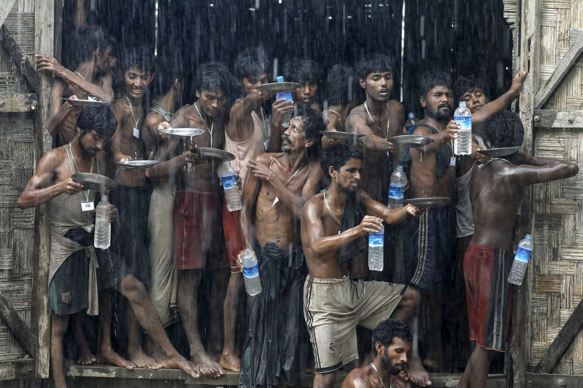 Migrants collect rain water at a temporary refugee camp near Kanyin Chaung jetty, outside Maungdaw township, Myanmar, on June 4, 2015.
