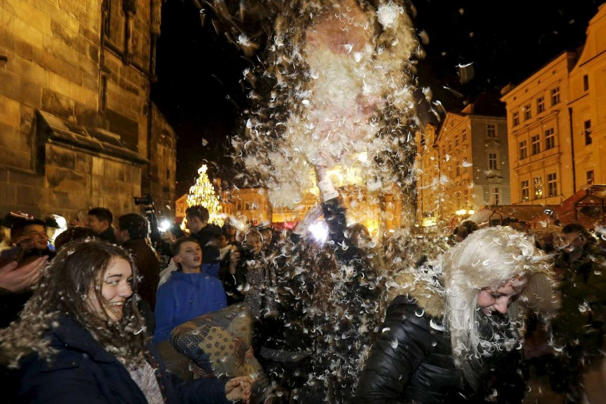 People take part in a four minute flash mob pillow fight at the Old Town Square in Prague.