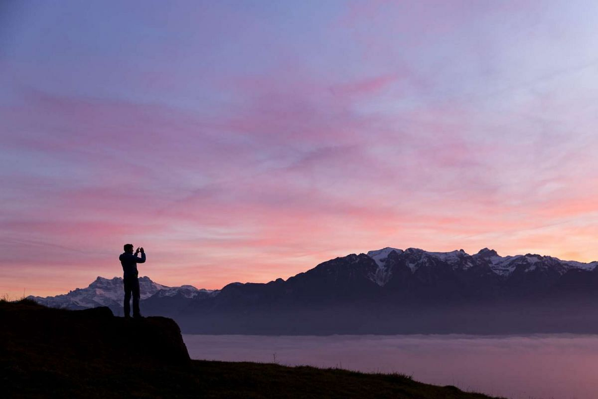 A man takes a picture of the sea of a fog that covers the Geneva Lake with the Swiss-French Alps in the background and the sun setting at Jongny above Vevey, Switzerland on Dec 22, 2015.