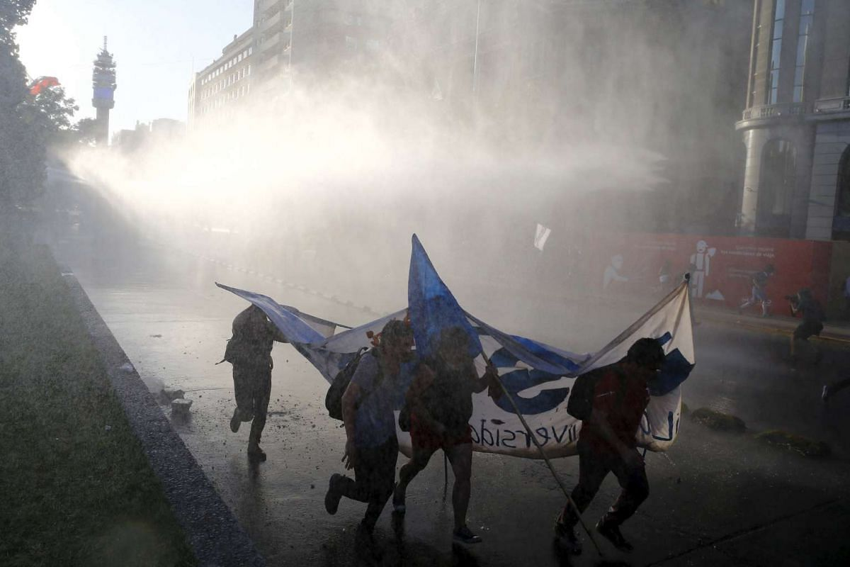 Students run away as a riot police vehicle releases a jet of water during a protest against the government to demand universal free education and changes to the education system in Santiago, Chile on Dec 22, 2015.