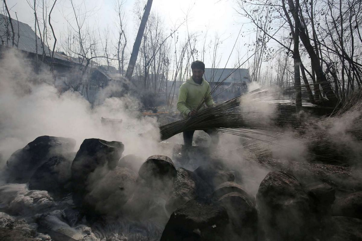 A Kashmiri Muslim man boils wicker sticks to soften its skin, prior to using them for making Kangris on the outskirts of Srinagar, the summer capital of Indian Kashmir on 22 Dec, 2015.