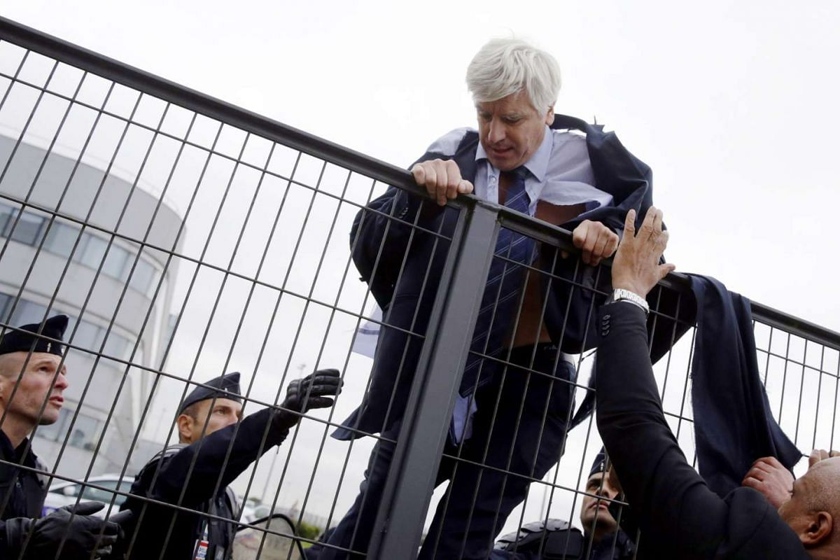 An Air France director is helped by security and police officers to climb over a fence, after several hundred employees stormed into the offices of Air France, in Roissy-en-France, on Oct 5, 2015.