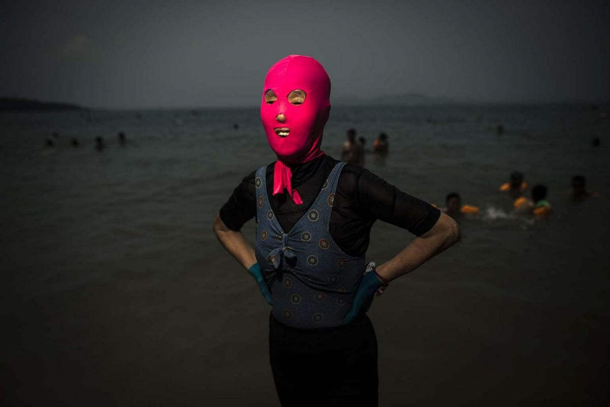 A woman wearing a facekini at the beach in Qingdao, eastern China's Shandong province, on July 24, 2015.