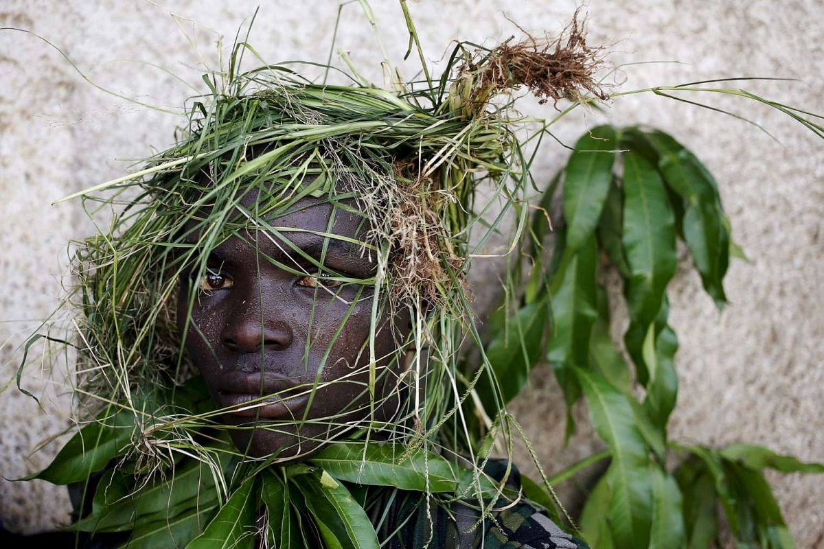 A protester wearing grass around his face to obscure his identity during a protest against President Pierre Nkurunziza's decision to run for a third term, in Bujumbura, Burundi, on May 11, 2015.