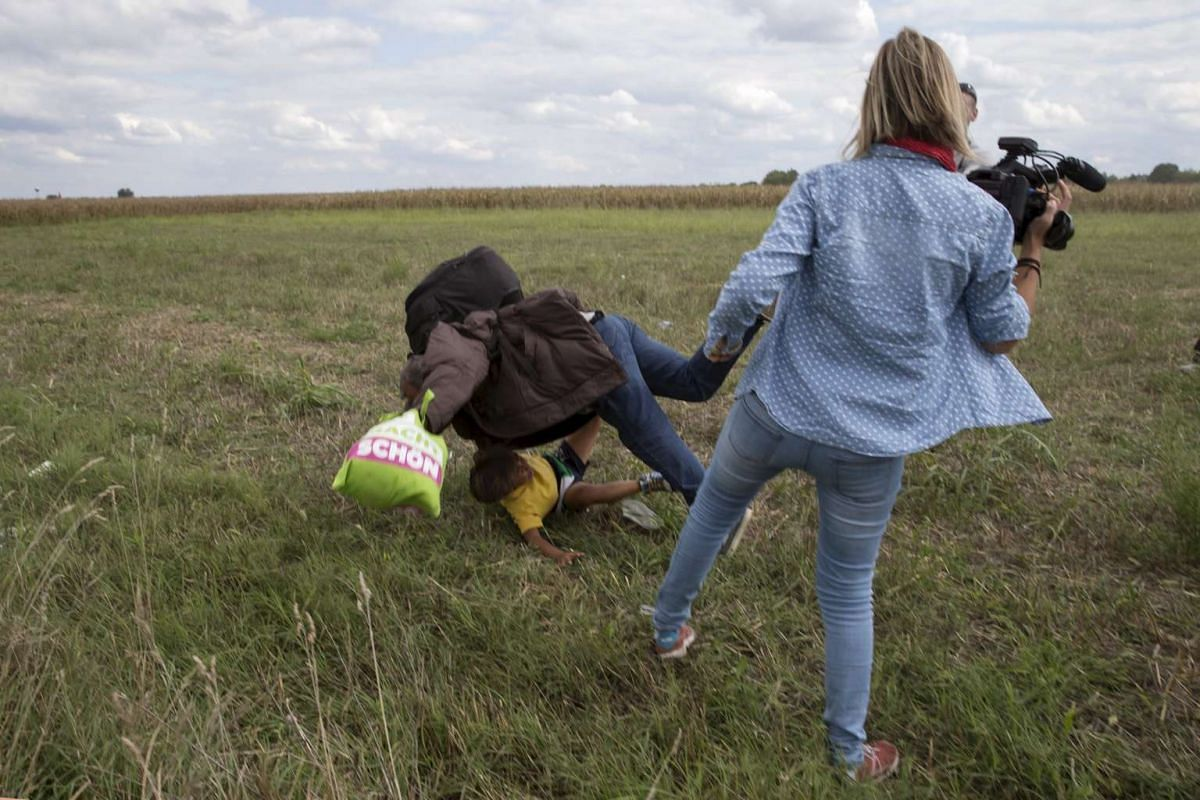 A migrant carrying a child falling after being tripped by TV camera operator Petra Laszlo while trying to escape from a collection point in Roszke village, Hungary, on Sept 8, 2015.