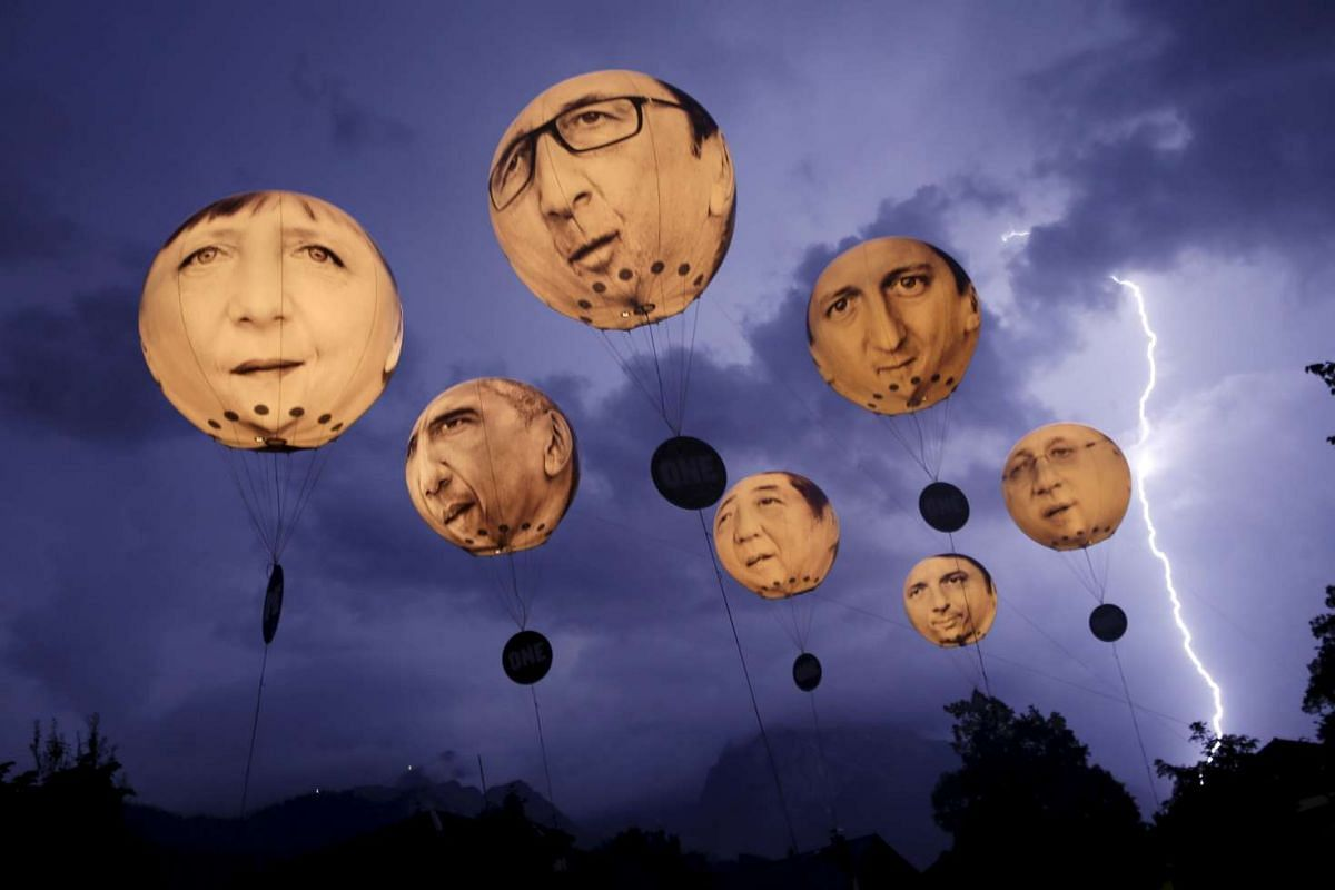 """Lightning striking the Alpine mountains over Garmisch-Partenkirchen as balloons, made by the """"ONE"""" campaigning organisation, depicting leaders of the G7 countries are inflated in Garmisch-Partenkirchen, Germany, on June 7, 2015."""