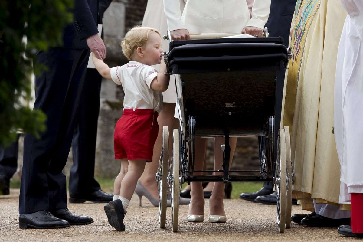 Britain's Prince George looking into the pram of his sister Princess Charlotte after her christening at the Church of St Mary Magdalene in Sandringham, Britain, on July 5, 2015.
