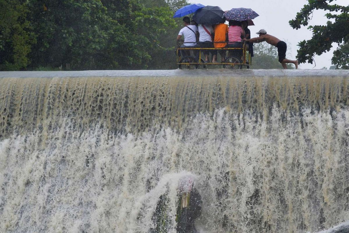 Residents crossing a swelling dam in Las Pinas city, metro Manila, Philippines, on Oct 19, 2015.