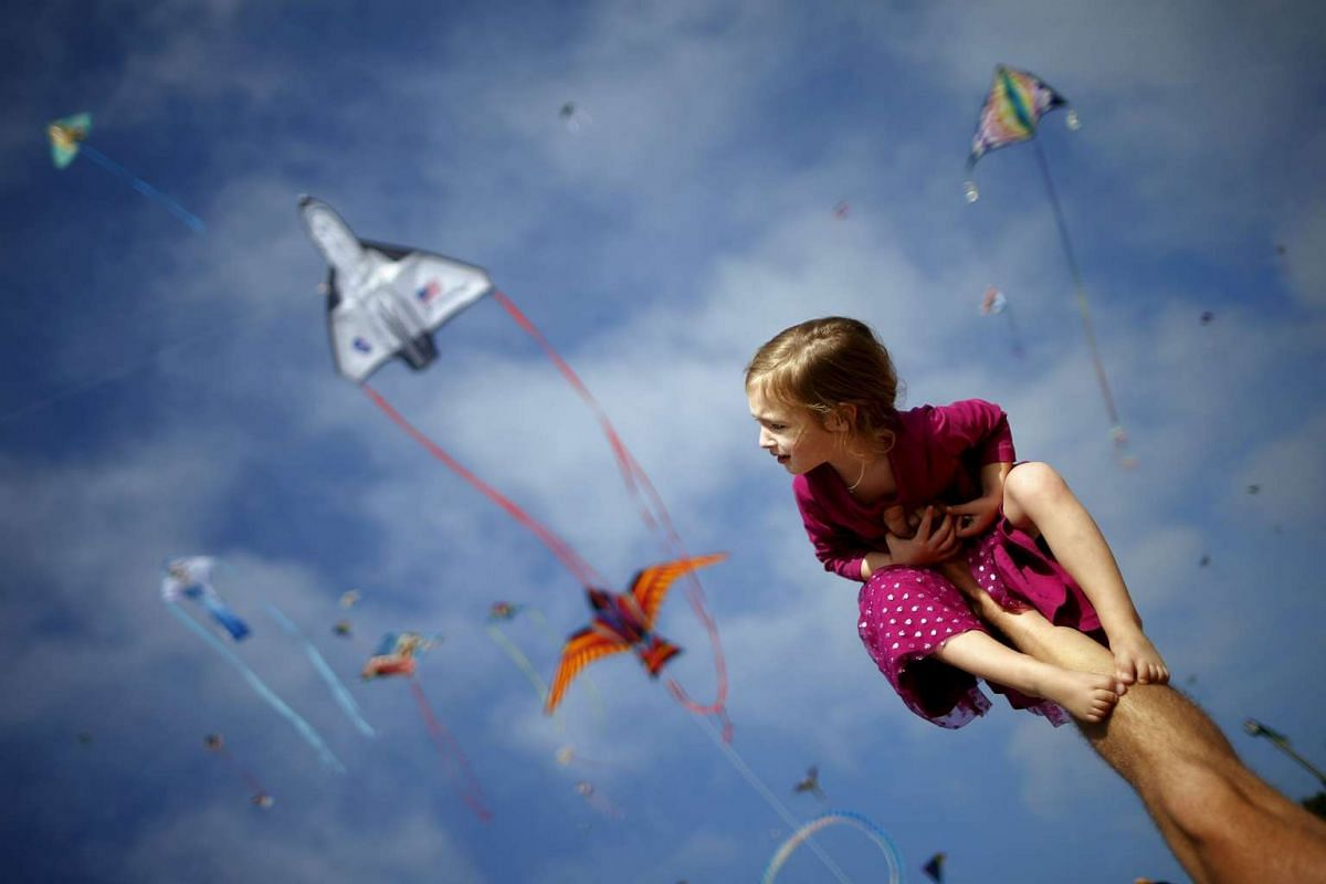 A girl sitting on her father's leg at a kite festival in Redondo Beach, California, United States on March 8, 2015.
