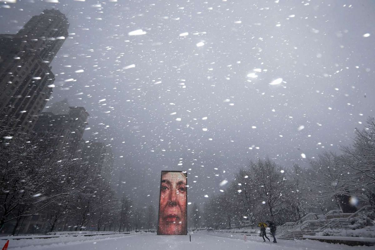 Two men walking past the Crown Fountain in blizzard-like conditions in Chicago, Illinois, United States on Feb 1, 2015.