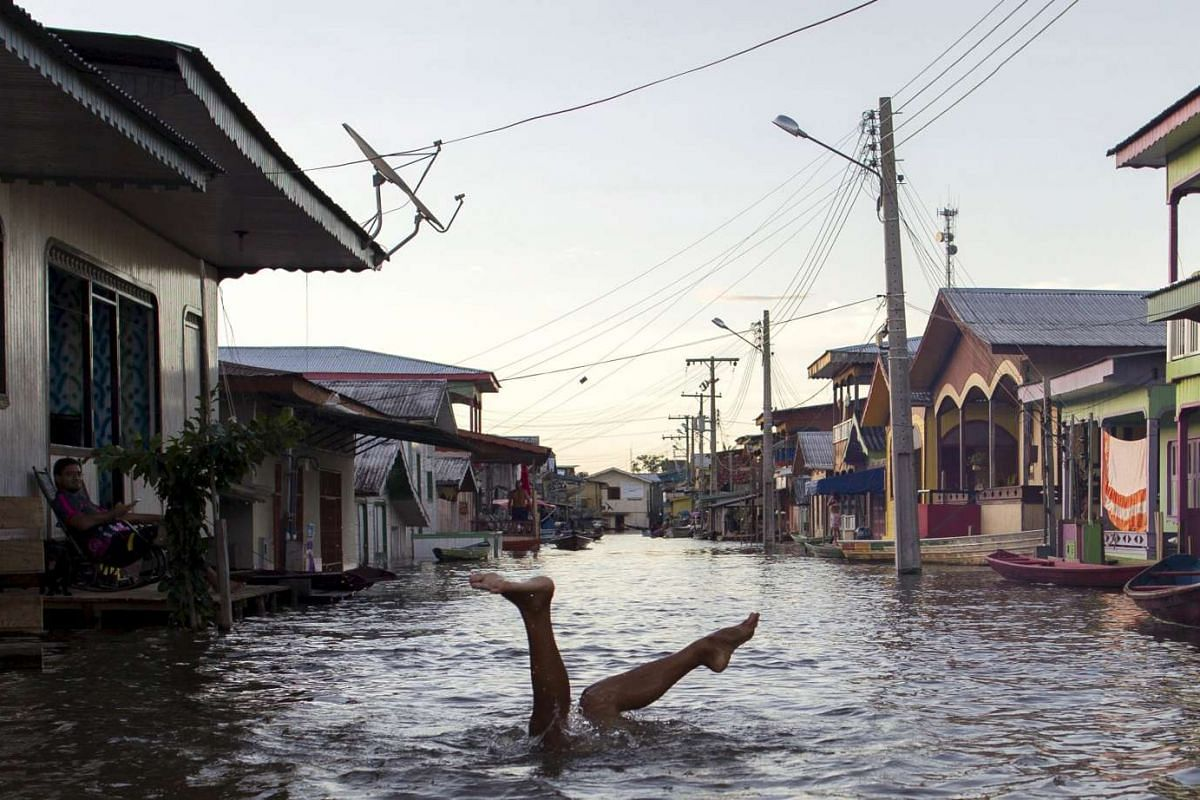 A child in a street flooded by the rising Rio Solimoes, one of the two main branches of the Amazon River, in Anama, Amazonas state, Brazil on June 3, 2015.