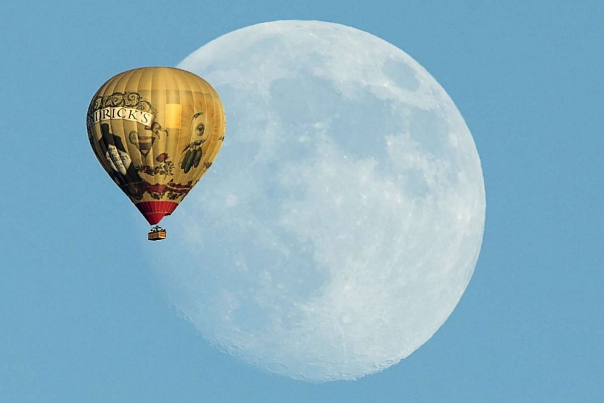 A hot air balloon floating past a rising moon over Rancho Santa Fe, California, United States, on Sept 25, 2015.