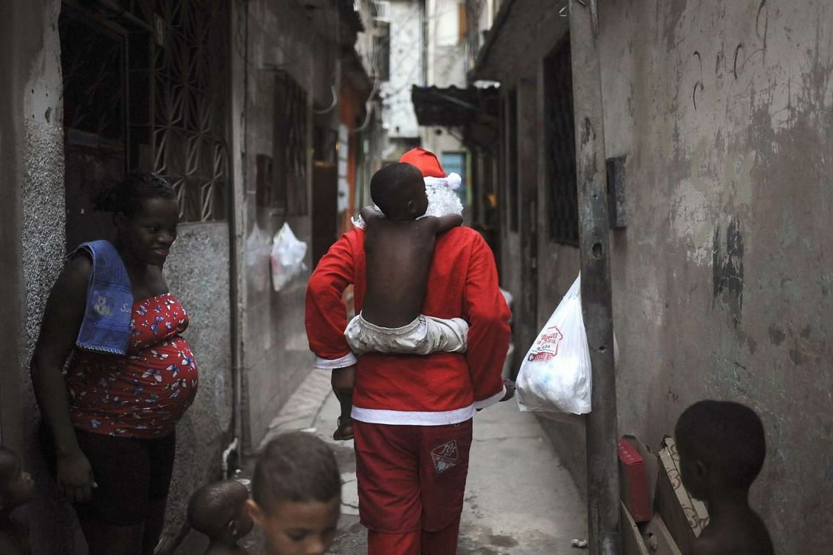 Leandro Wendell dos Santos, 14, wearing a Santa Claus costume, playing with kids as he walks along the alley of the Mare slums complex to distribute presents to children in Rio de Janeiro, Brazil on Dec 23, 2015.