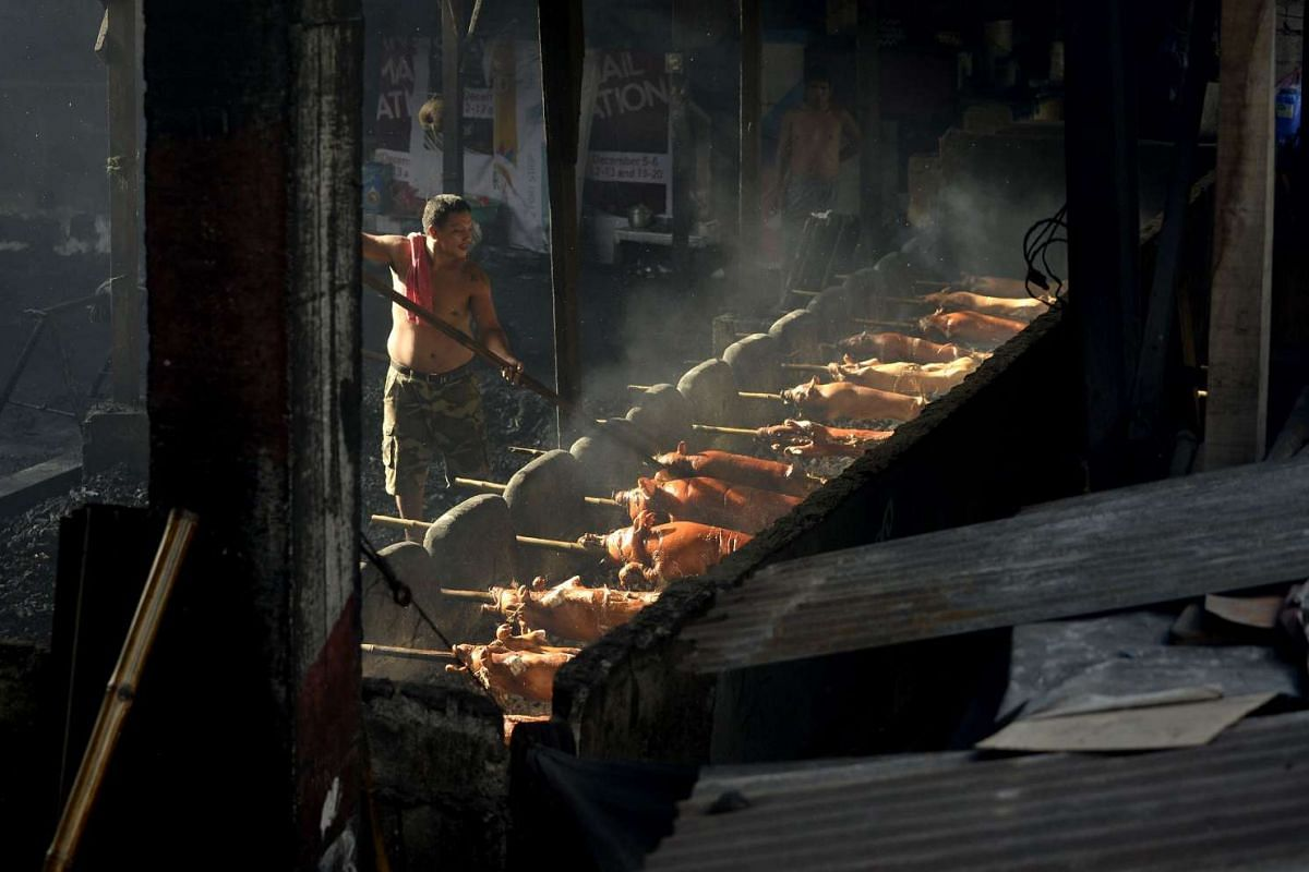 A worker turning bamboo skewered pigs as they are roasted over hot coals in Manila on Dec 23, 2015.