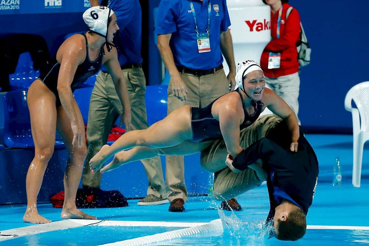 US players pushing head coach Adam Krikorian into the pool after they defeated the Netherlands in their women's water polo gold medal match during the Aquatics World Championships in Kazan, Russia on Aug 7, 2015.