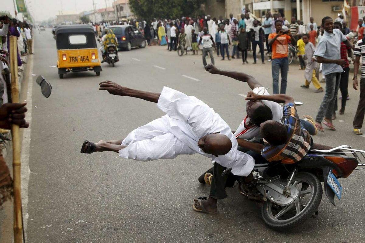 Supporters of the presidential candidate Muhammadu Buhari and his All Progressive Congress hitting another supporter on a motorbike during celebrations in Kano, Nigeria on Mar 31, 2015.