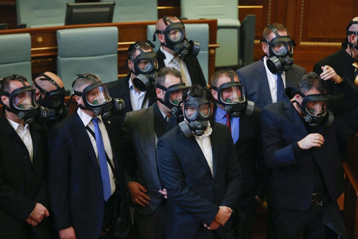 Kosovo police officers wearing gas masks during a plenary session at Kosovo's parliament in Pristina, Kosovo, on Dec 14, 2015.