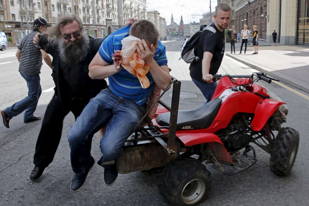Anti-gay protesters attacking a gay rights activist during an LGBT community rally in central Moscow, Russia, May 30, 2015.