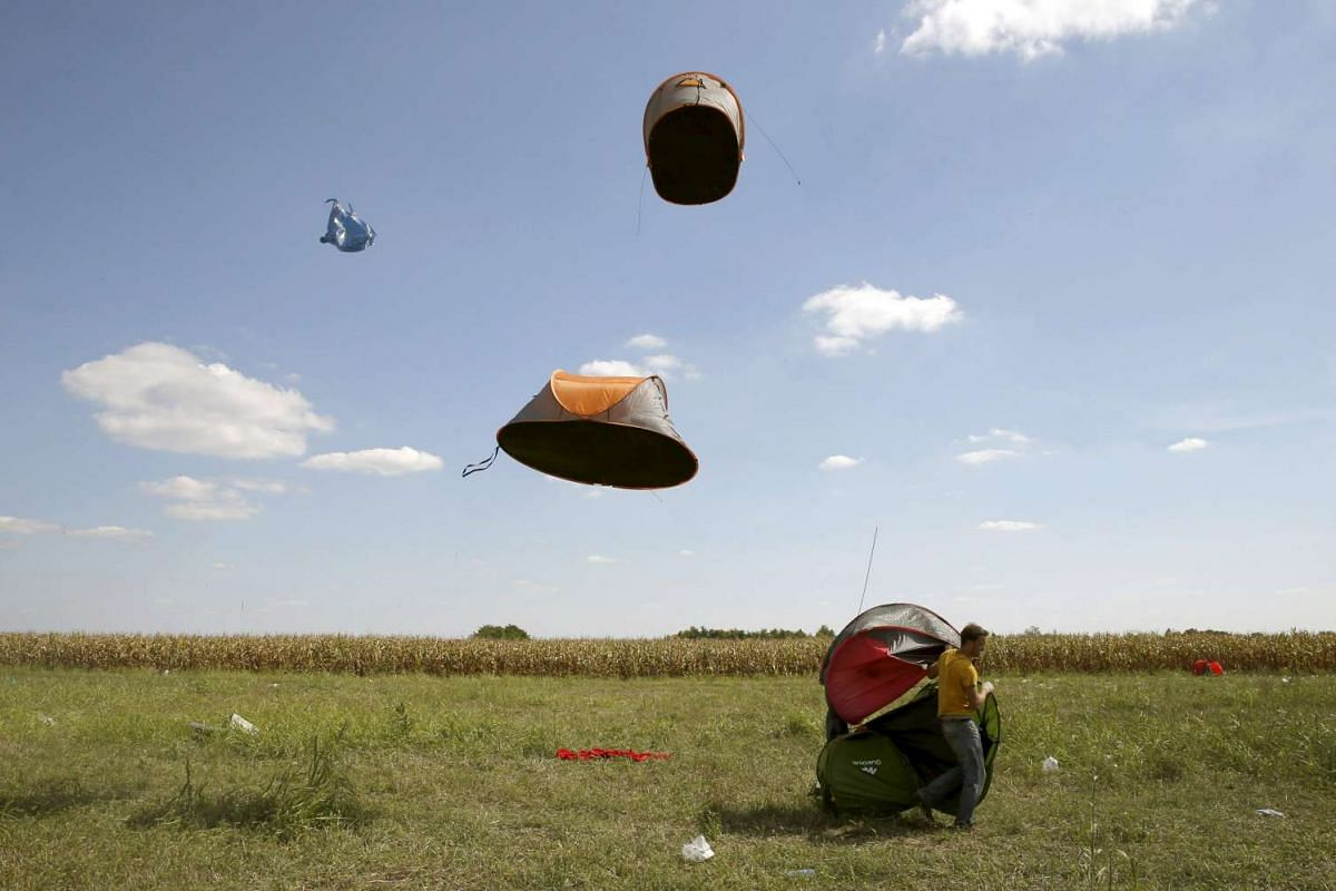 Migrants' tents being blown off by the wind near a collection point in the village of Roszke, Hungary on Sept 9, 2015.