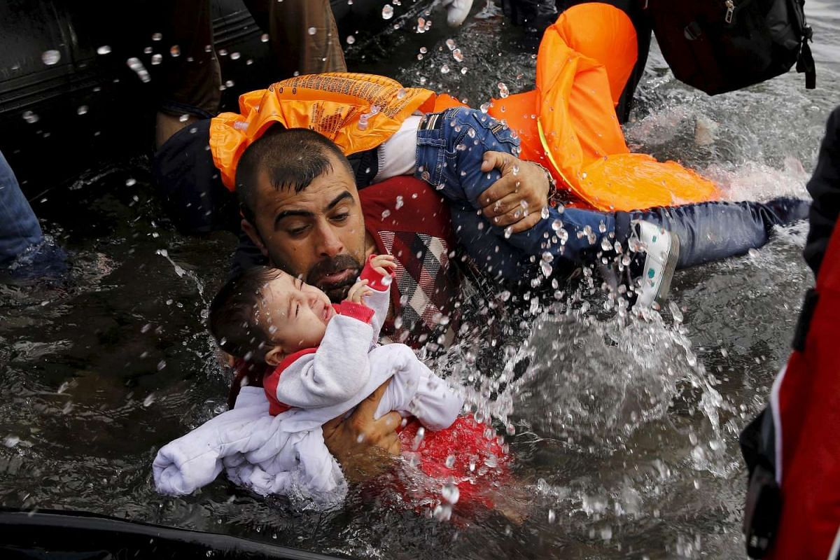 A Syrian refugee holding on to his children as he struggles to walk off a dinghy on the Greek island of Lesbos, after crossing a part of the Aegean Sea from Turkey to Lesbos on Sept 24, 2015.