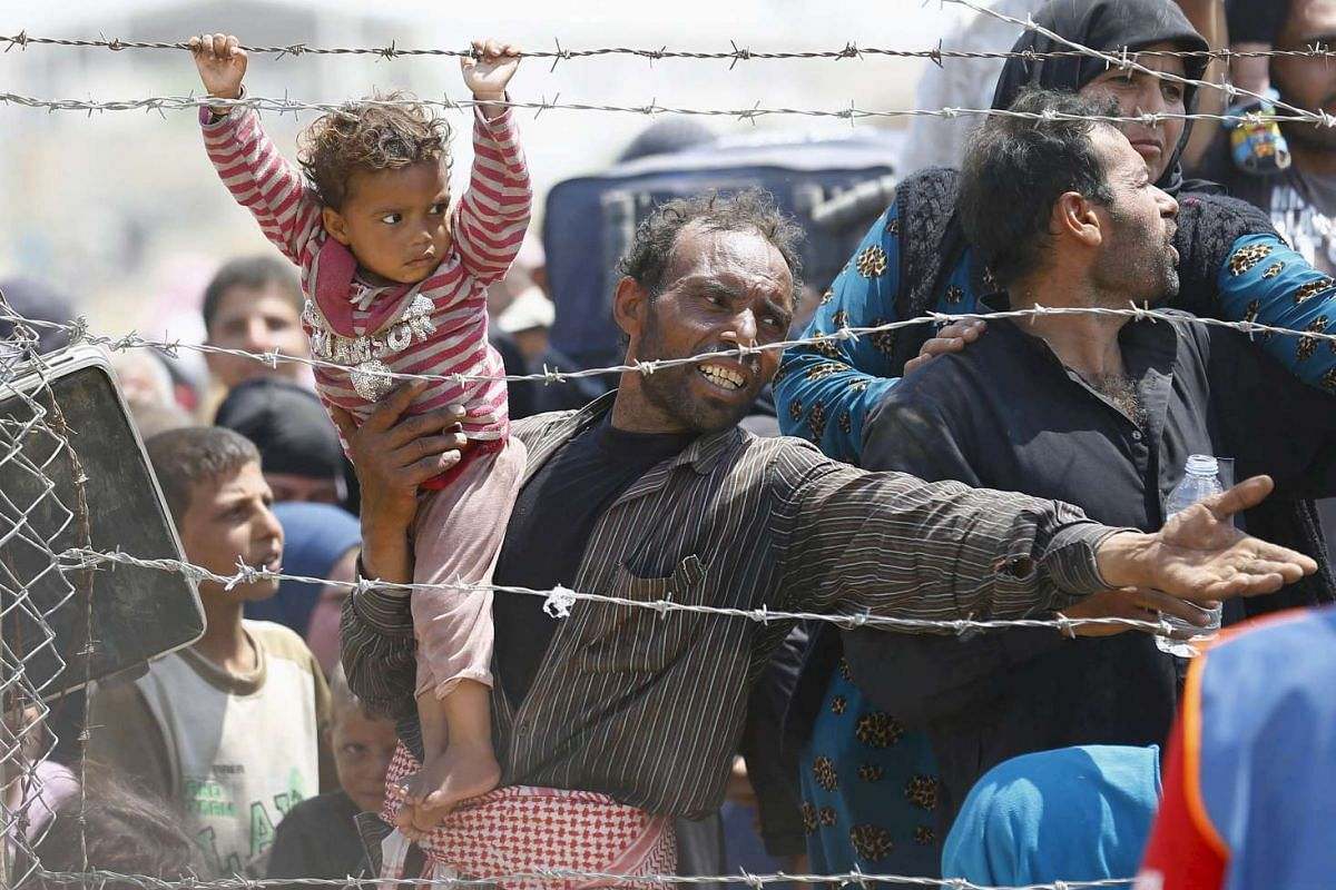 A Syrian refugee reacting as he waits behind border fences to cross into Turkey at Akcakale border gate in Sanliurfa province, Turkey, on June 15, 2015.