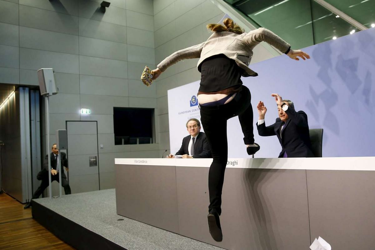 A protester jumping on the table in front of the European Central Bank President Mario Draghi during a news conference in Frankfurt, Germany on April 15, 2015.