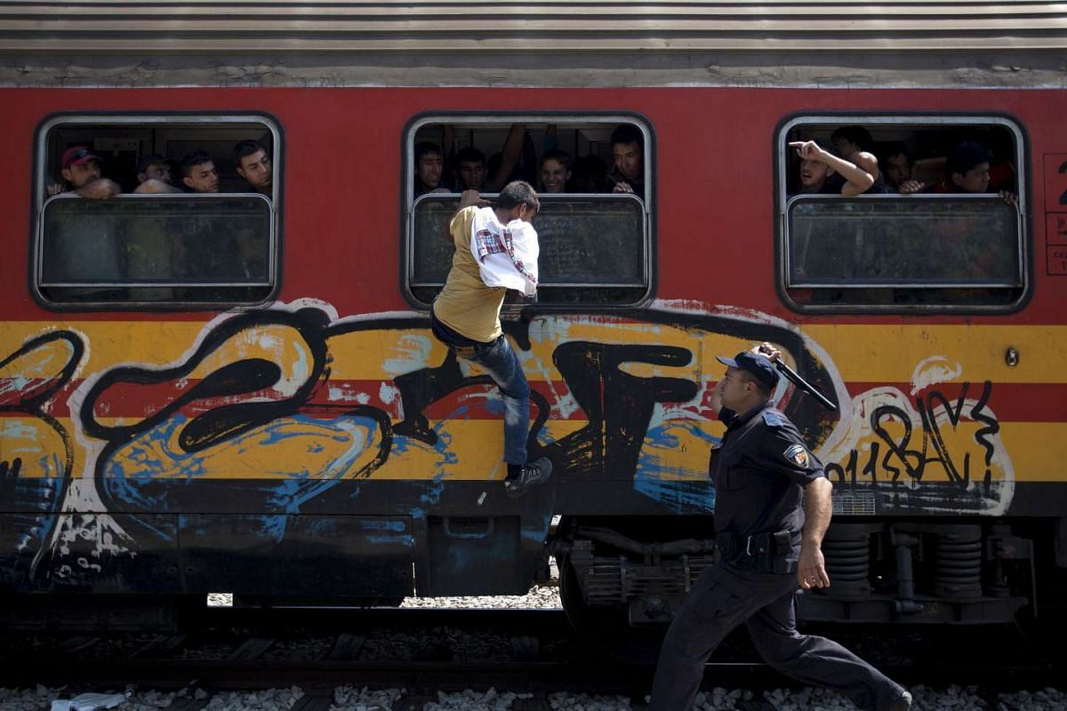 A policeman trying to stop a migrant from boarding a train through a window at Gevgelija train station in Macedonia, close to the border with Greece, on Aug 15, 2015.