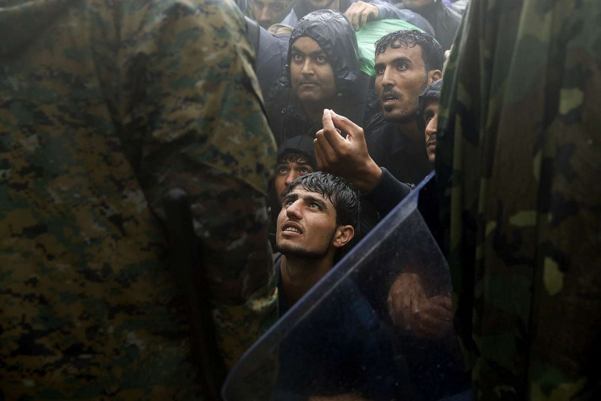 Migrants and refugees begging Macedonian policemen to allow passage to cross the border from Greece into Macedonia during a rainstorm, near the Greek village of Idomeni, on Sept 10, 2015.