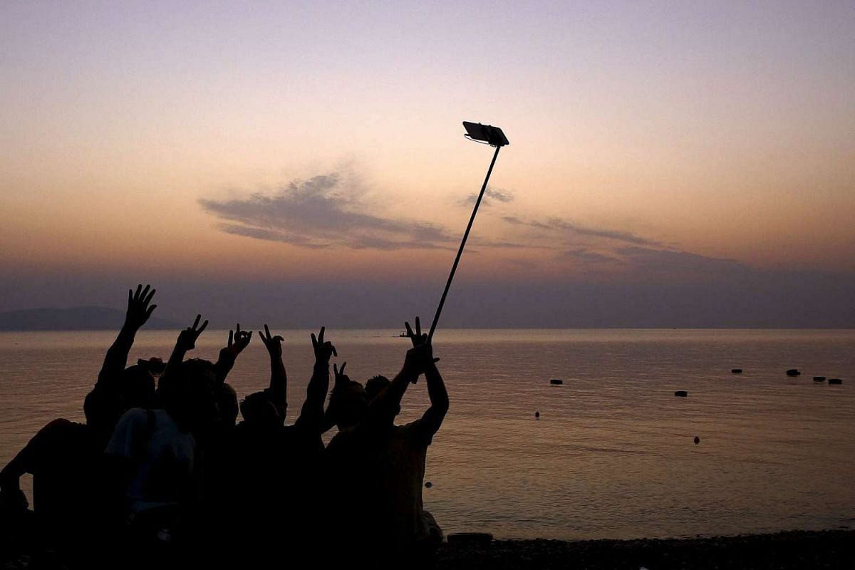 "Syrian refugees taking ""selfies"" moments after arriving on an overcrowded dinghy at a beach on the Greek island of Kos, after crossing a part of the Aegean sea from Turkey, on Aug 9, 2015."