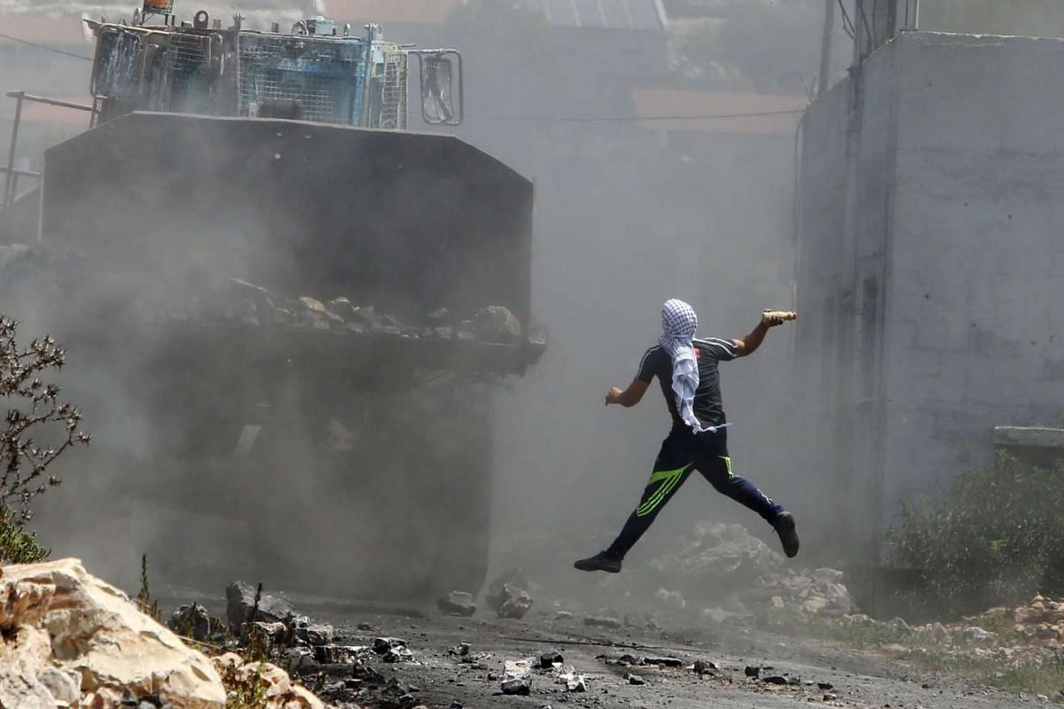 A Palestinian protester throwing a bottle filled with paint at an Israeli army bulldozer during clashes following a demonstration against the expropriation of Palestinian land by Israel in the village of Kfar Qaddum, near Nablus in the occupied West