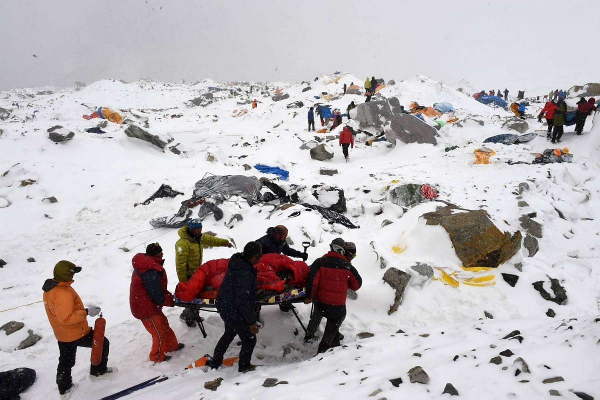 Rescuers using a makeshift stretcher to carry an injured person after an avalanche triggered by an earthquake flattened parts of Everest Base Camp on April 25, 2015.