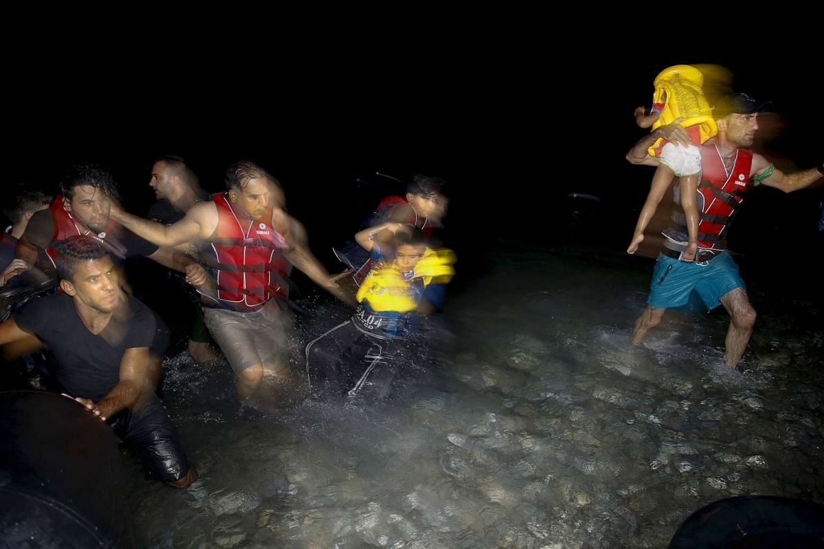 Syrian refugees carrying their children as they jump off a dinghy overcrowded with Syrian refugees upon arriving on a beach on the Greek island of Kos, after crossing a part of the Aegean sea from Turkey, on Aug 9, 2015.