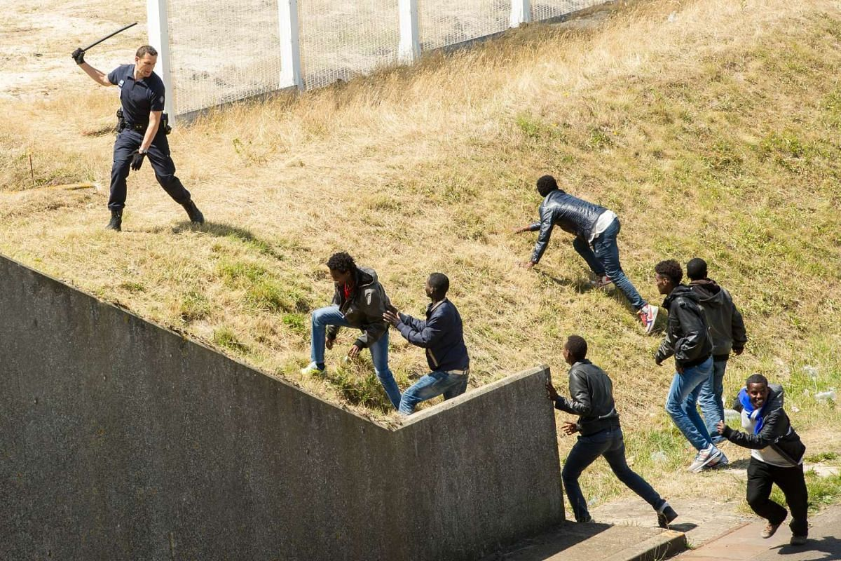 A French antirot police (CRS) officer trying to prevent illegal migrants from hiding in trucks heading for England in the French northern harbour of Calais, on June 17, 2015.