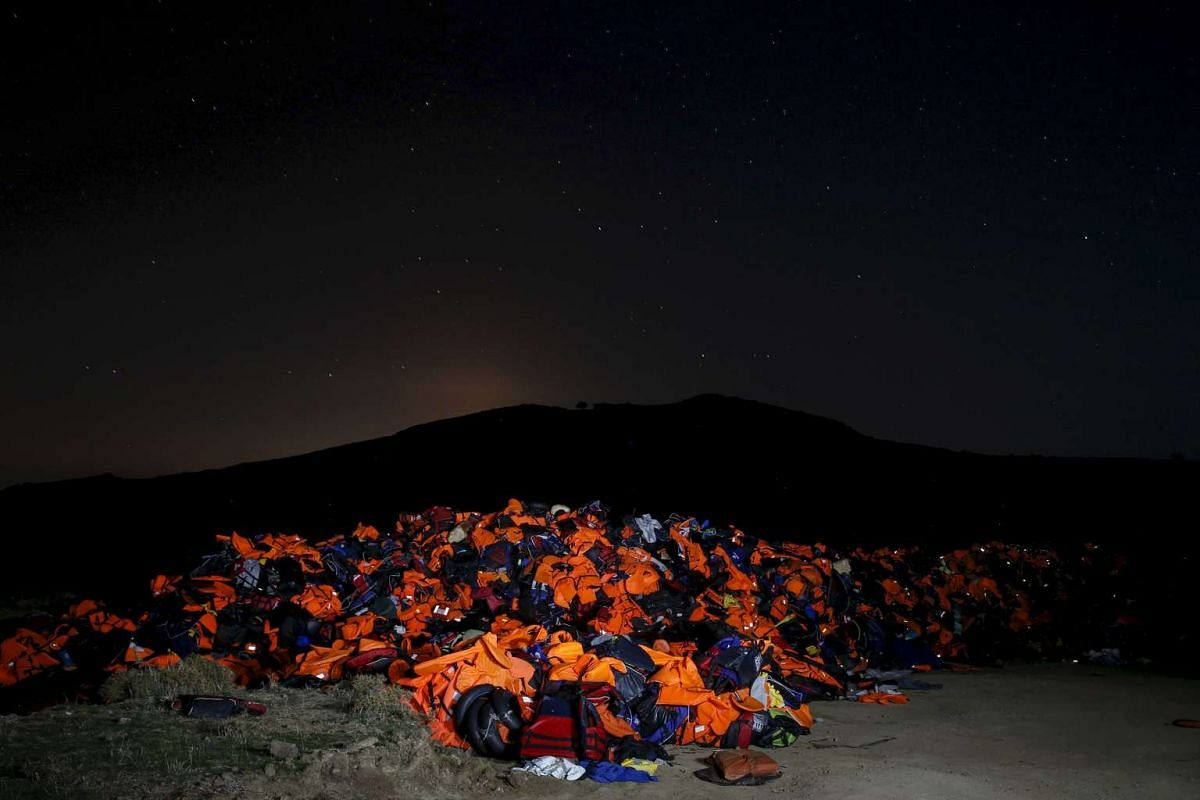 A long exposure photo showing thousands of lifejackets left by migrants and refugees, piled up at a garbage dump site on the Greek island of Lesbos, on Nov 9, 2015.