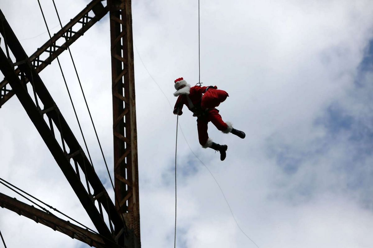 Firefighter Hector Chacon, 70, dressed as Santa Claus, descends from a 150m-high bridge to deliver gifts to children who live in poverty, in Guatemala, on Dec 23, 2015.