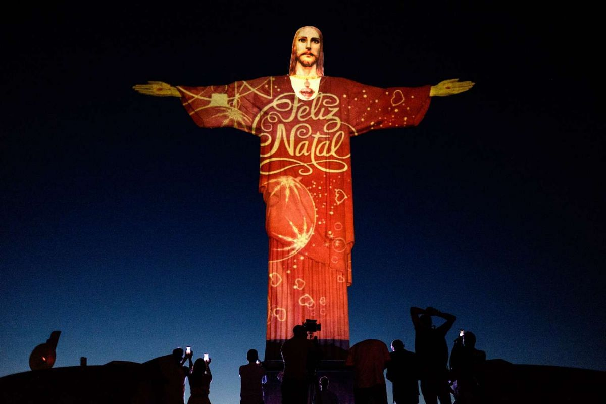 """People take pictures of the statue of Christ the Redeemer illuminated by Brazil-based French lighting designer Gaspare Di Caro, which reads """"Merry Christmas"""", in Rio de Janeiro, Brazil."""