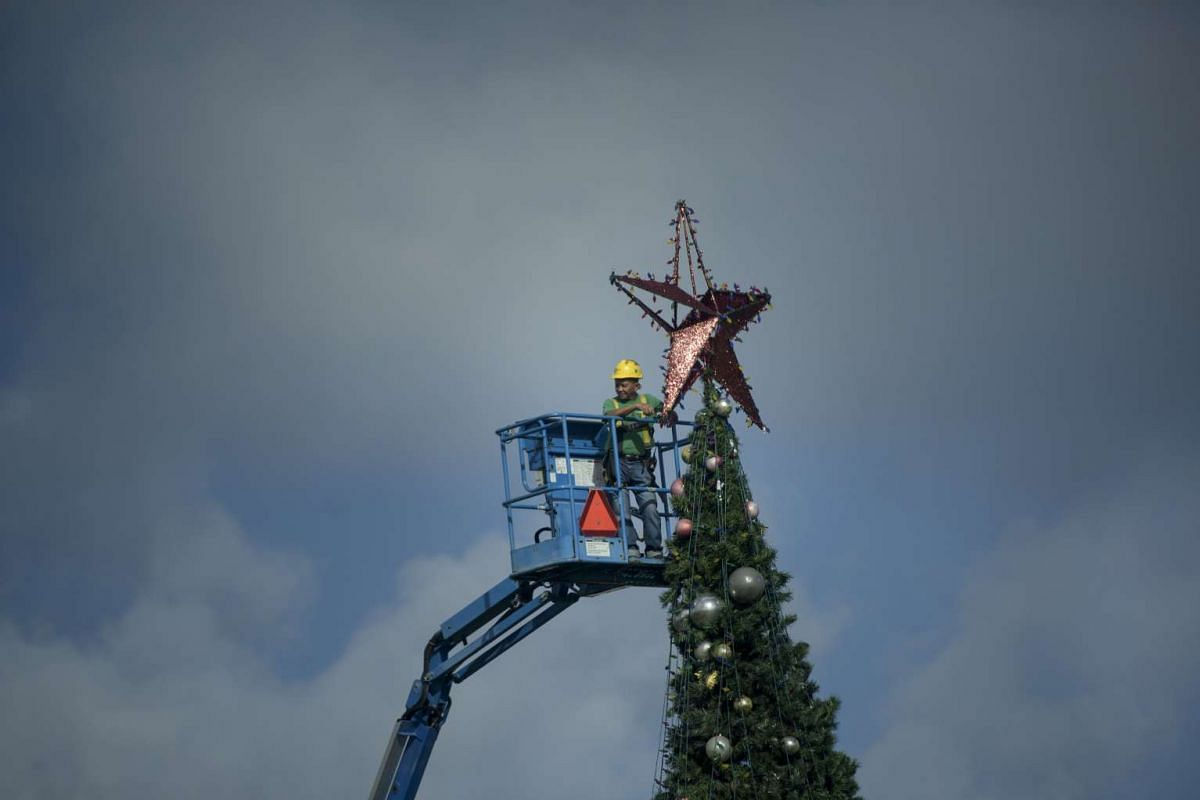 A worker attaching a star on a Christmas tree watches as a motorcade with United States President Barack Obama leaves the Marine Corps Base Hawaii on Dec 23, 2015, in Kailua, Hawaii.