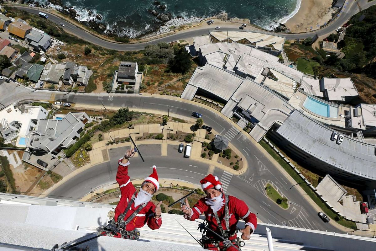 Workers wave as they clean the windows of a building dressed as Santa Claus in Vina del Mar city, Chile, on Dec 23, 2015.