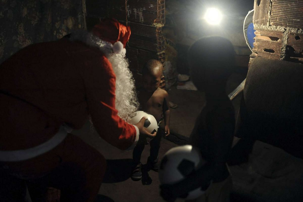 Volunteer Leandro Wendell dos Santos, 14, wearing a Santa Claus costume, distributes presents to children in Mare slums complex in Rio de Janeiro, Brazil, on Dec 23, 2015.
